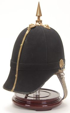 HELMET FROM A BRITISH VICTORIAN TO EDWARDIAN ERA COLONEL'S UNIFORM FOR THE 3RD EAST KENT REGIMENT THE BUFFS. Black wool covered Home Service helmet with brass spike with cruciform base, trim and chin chain. Obverse with a brass and silver regimental plate. Interior maker marked and with leather sweatband. Red wool tunic has buff collar, cuffs and piping trimmed in gold braid with silvered regimental collar insignia, and gold cord shoulder boards with rank insignia. Complete with gold and…