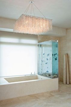 The large crystal light fixture suspended over the bathtub in Kanye West's bathroom gives the space a very glamorous feel~