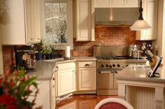 This charming kitchen utilizes exposed brick to offset the creamy cabinetry and use of stainless steel appliances while still exuding a cozy cottage like feeling. Windows bring in plenty of light for the small space. Glass Kitchen, New Kitchen, Kitchen Ideas, Kitchen Sink, Kitchen Stuff, Kitchen Cabinets, Kitchen Hacks, Kitchen Decor, Exposed Brick Kitchen