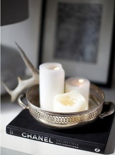 White candles in a dish next to a fav designer.