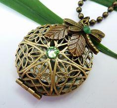 Edle Halskette mit einem filigranen Medaillon aus bronzefarbenem Metall. Der schöne Blatt-Anhänger aus Messing und der Libellen-Anhänger verleihen ...