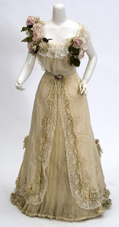 """""""Evening gown of cream colored silk faille with chiffon inlets, pleated off shoulder style enhanced by large bunches of white velvet ribbon """"flowers.  1907"""" (quote)"""