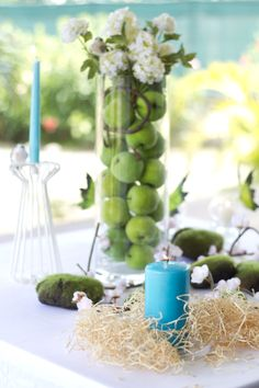 Table centerpiece with green apples and mimosa in a vase, matching turquoise candles, cherry blossoms and moss table spread. Green, Turqoise and Pink. Photo Credit : A. Mordant - Click here to read more on the Blog: http://www.wedotahiti.com/table-decor-for-a-summer-garden-party/ #tahitiweddingplanner #tahitiweddingpackage