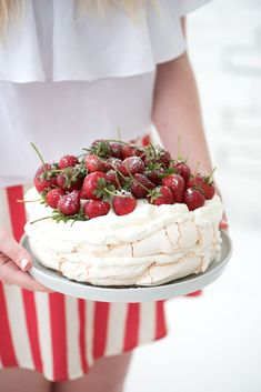 Pavlova topped with fresh strawberries and whipped cream.