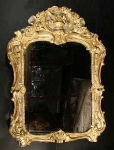 Mirror #LouisXV in carved and #gilt wood. #Decor of a molding with an alternating patterns of shells. Carved flowers on the pediment. #Original gilding and original mercury glass. #18th century. For sale on Proantic by Olivier Camus Antiquités.