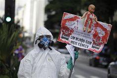 """Un manifestante usa un traje protector y mascarilla mientras muestra un cartel en portugués que dice """"Un mundo mejor según Monsanto es un mundo con más cáncer"""", en las calles de Sao Paulo, Brasil."""