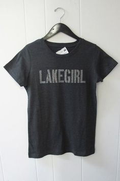 lakegirl Sparkle Tee | Show your bling with the lakegirl Sparkle Tee for a fun time on the lake, dock or at the concert in town! Charcoal gray with silver logo. Scoop neck. Short sleeves. 60% Cotton/40% Polyester. Sizes S-XL.