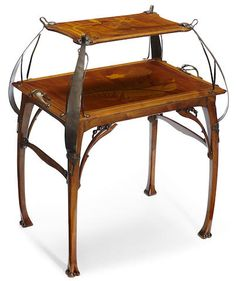 A Léon Benouville mahogany, marquetry and brass étagère circa 1900. This art nouveau piece celebrates curves and the use of decorative elements. It also incorporates a metal component, which was very popular at the time. Art nouveau made metals feel more organic and removed them from the cold industrial stereotype.