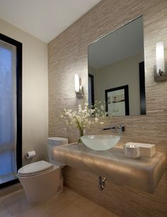 Underlit stone vanity with glass vessel sink creates a feeling of calm glamour.