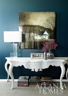 Deep colored wall, traditional console painted white and a contemporary lamp-eclectic