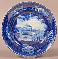 """Historical Staffordshire China Blue Transfer """"Chief Justice Marshall"""" Paddleboat Plate. Enoch Wood & Sons, England, ca.1819 - 1846. Unmarked. Depicting the steamboat Chief Justice Marshall of the Troy line, operating between Albany and New York, with shell border. 10"""" diameter. Condition: Very Good. Conestoga auctions. October 25, 2014. Lot 108. Estimate $200-$400. Sold for $605."""