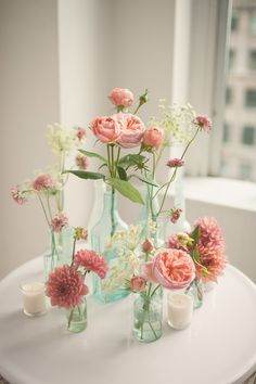 pink floral arrangements in glass bottles, photo by MGB Photo http://ruffledblog.com/manhattan-loft-wedding #centerpieces #flowers