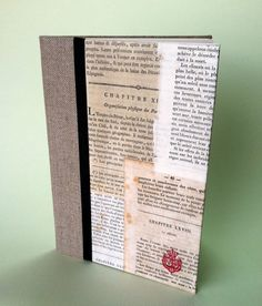 pamphlet-sewn notebook decorated with patchworked text pages from various 18th century French books, so probably cotton or linen paper. Inside are 20 pages of smooth ivory paper, and sturdy linen bookcloth covers the back and part of the front.