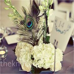 White floral centerpiece with peacock feather