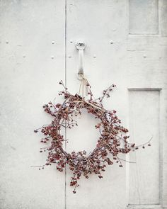Minimalist Red Berry Wreath on a white carriage cottage door. Fresh New year decor. Real simple love clean circle pastel. Berries and twigs.