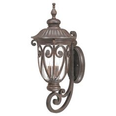Showcasing eye-catching scrolling details, brown finish, and a clear seeded shade, this lovely wall lantern casts an inviting glow over your front walk or ve...