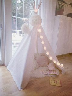 Pure white tee pee looking beautiful with added lights & other accents. #girls #readingnook