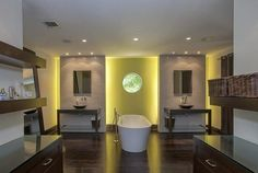 | Matt Damon's Miami Waterfront Home | The master bath has an interesting porthole window and a freestanding, modern tub flanked by his and hers sinks.