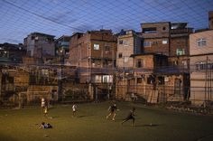 """Youths play soccer in the Campo da Lixeira or """"Trash Field"""" soccer field in Rio de Janeiro, Brazil. In some places, barefoot kids sprint on artificial grass installed by the city government or non-governmental organizations whose social projects focus on the sport. Photo: AP Photo"""