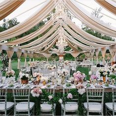 Beautiful outdoor open marquee garden wedding reception styling with lots of crystal chandeliers, draping and fresh flowers #wedding #gardenwedding #marquee #outdoorwedding #weddinginspo #weddingstyle #weddingstyling #weddingdecor #tablesetting #tablescape #weddingreception #eventstyling #flowers #flowercentrepieces #chandeliers
