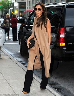 Victoria Beckham wearing a stylish long beige sleeveless jacket from her own FW 2013 collection.. along with black trousers, and nude wedge heels.