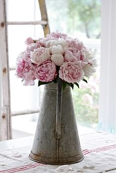 I love the idea of old, vintage jars (and in this case a watering can), with flowers in them.