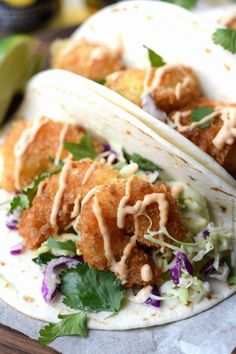 These Crispy Shrimp Tacos with Cilantro Lime Slaw will seriously rock your world! A quick and easy weeknight meal that is sure to become a family favorite.