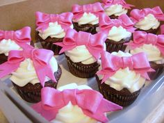 Chocolate cupcake with buttercream frosting and pink fondant bows