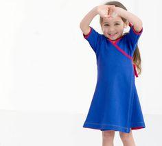 Karmakid: fröhliches biologisches Wickelkleid blau mit roten Bändern. Bei Karmakid findet Ihr ausgefallene, schöne und mit Liebe hergestellte Kleidungsstücke für euer Kind, alles fair, ökologisch, antiallergen.
