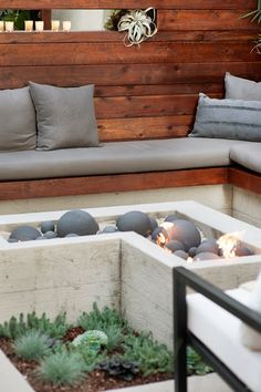 """In this yard, Prange built a banquette that mimics the L-shape of the concrete fire feature so you can enjoy the flames from any angle. """"Keep your seating low, even as low as 12 inches off the ground, to create a relaxed experience,"""" he says. The chic ceramic spheres nestled inside the fire pit don't just add visual interest, they help radiate heat."""