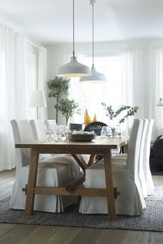 Classic white dining space with rustic and industrial touches - featuring the RANARP pendant lamp and MÖCKELBY oak table from IKEA,