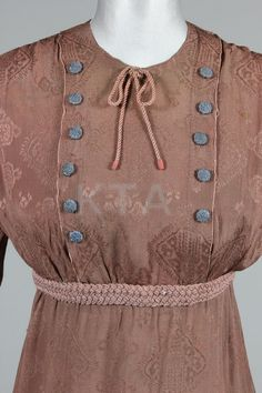 An A. Groult brown damask day dress, circa 1912, labelled to the broad grosgrain waistband, 31, Rue d'Anjou, the high waistline outlined in pink/beige woven braid, cord bow to neck, with rows of grey-blue silk embroidered buttons to the bodice and cuffs, bust 86-92cm, 34-36in