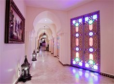 Classy Moroccan Home. Beautiful lanterns in the hallway, and a pretty glass/wooden door.