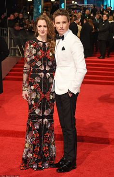 The happy couple: Leading the suave men on the carpet was Eddie Redmayne who looked stylis...