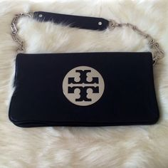 Tory Burch Reva Clutch Reva clutch in black leather and silver hardware. This clutch is a classic and the straps are removable so it can be worn as a shoulder bag as well as a clutch. In amazing condition, I wore this bag about a handful of times, not even enough to break in the leather. It is almost like new. It has a couple of tiny scratches on the front as you can see on the pic and a couple of make up spots in the inside, I didn't try to remove them but it looks like it comes off easily…