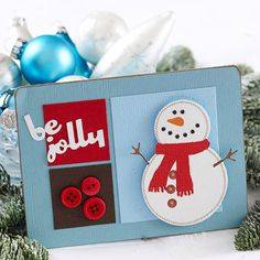 Snowman Christmas Card: This smiling snowman Christmas card will warm the hearts of friends and family. Simple paper squares, a die-cut snowman, and festive buttons make it easy to send off holiday greetings this Christmas.