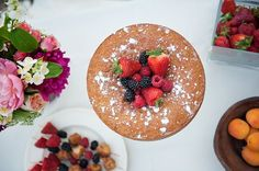 Naked cake topped with fresh berries and dusted with powdered sugar | Photo by Brooke Schultz
