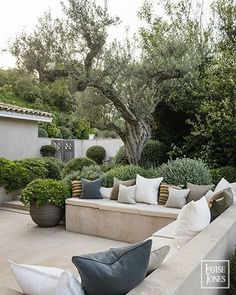 Built in concrete bench seating. Light coloured pavers. Grey/green plant material. Mediterranean feel.