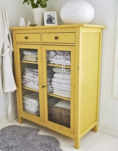 Painted yellow cabinet used for linens <3