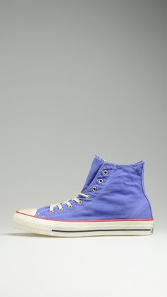 Purple Chuck Taylor lace-ups high top sneakers in canvas, contrast white laces, metallic eyelets, rubber sole, red trims on the platform.