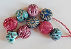 The set consists of =9 beads of ceramic and stoneware ,hand carved ,have raspberry and turquoise glazes . Mª Carmen Rodriguez Martinez ( Majoyoal ) https://www.facebook.com/groups/CeramicArtBeadMarket