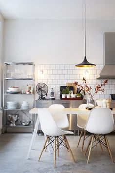 White dine-in #kitchen with white square tile, open shelving, stainless steel storage, #Eames dining chairs | Photo by Patric Johansson for Plaza Interiör (Sweden)