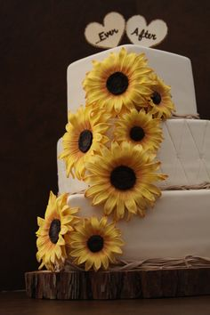 Sunflower Wedding Cake - Bride wanted a rustic cake with raffia and sunflowers.  Everything is fondant except for the toppers which were wood signs.  Sunflowers were made with the help of a tutorial from SugarEd Lagniappe.  Wood base was supplied by the bride. TFL!