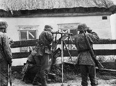 1941, Union Soviétique, des Waffen-SS ont mis une MG-34 en batterie sur un trepied dans un village |