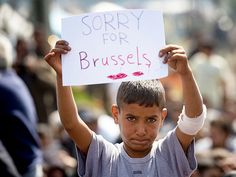 A young boy – a member of a makeshift refugee camp at the Greek-Macedonia border near Idomeni, Greece – holds a sign expressing solidarity with Belgium on Tuesday.