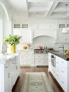 Love this all-white kitchen with gray and white carrara marble counter tops, traditional white cabinetry with millwork, an arched concealed oven range hood, paned glass front upper cabinets, a kitchen island with built-in sink in the dark gray concrete counters, glossy medium hardwood floors, shiny silver and white modern industrial pendant light fixtures and a neutral-hued ivory and beige floor rug runner.