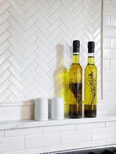 A basic white subway tile backsplash gets spiced up with a herringbone inset. Mixing a variety of white tiles creates a cohesive look that isn't jarring. The additon of a marble shelf offers the perfect spot to store oils and spices close to the range.