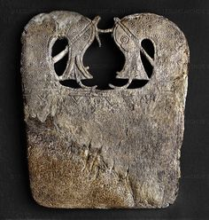 Whalebone plaque, Viking, 9th century, decorated with a pair of openwork horses' heads at the top and incised with ring-and-dot and geometric designs. It is thought that these plaques were used as boards for smoothing folds and seams in linen clothing with the aid of bun-shaped glass smoothers. This example is from a barrow burial at Lilleberge, Namdalen, Norway.