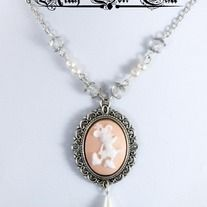 """Minnie Mouse is framed in a filigree pendant measuring approximately 40x30mm that features an imitation pearl dangle. I have secured the pendant to a 16"""" silver plated chain adorned with faceted crystals and peach lab created pearls to match the lovely white on peach cameo! The necklace secures a..."""