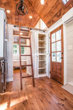 The Ridgewood's kitchen is equipped with a custom concrete countertop, full size refrigerator, dishwasher, gas range with hood, and pantry storage.